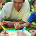 stock-footage-happy-family-drawing-together-while-lying-on-the-grass-in-a-park