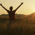 Young_Man_Walking_and_Raising_Hands_in_the_Field_590