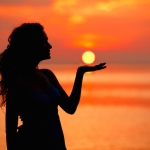 Happy Woman enjoying in Sea Sunset. Silhouetted against the sunset, sunrise. Sun on the palm