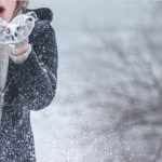 Woman-blowing-snow-hands-coat-1024x650