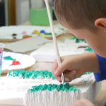 boy-is-painting-attentively-with-brush-kids-creating-hand-made-products-for-charity-auction-katedra-podwyszenia-w-krzya-puppets-and-actor-theater_vyp5miryg__F0000