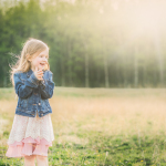 backlit-photo-of-young-girl-wearing-a-jean-jacket-in-a-field-by-Gina-Yeo